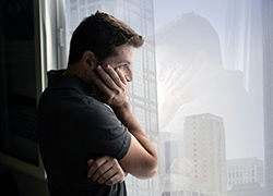 man looking out the window depressed