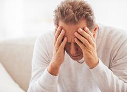 man holding head depressed