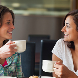 two-women-talking-with-coffee-in-hand-social-support