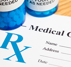 medical-prescription-with-blue-pill-bottle-on-top-of-paper-prescription