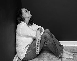 woman sitting on floor holding pillbox looking upset