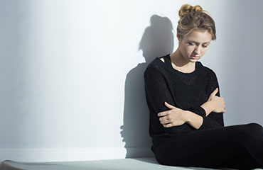 Girl sitting against wall with hands crossed