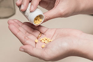 Person pouring out yellow klonopin like pills